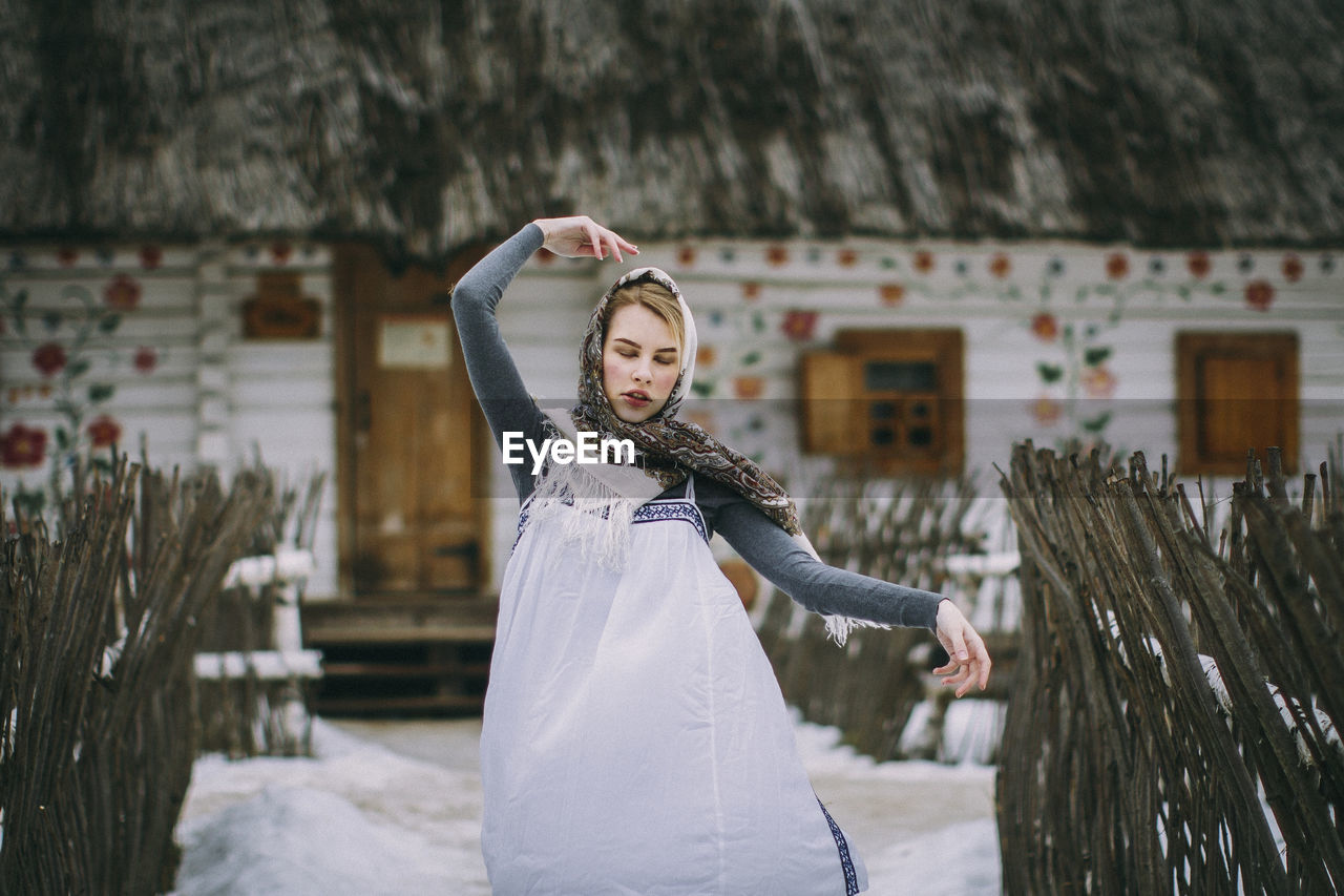 Woman with eyes closed standing in snow