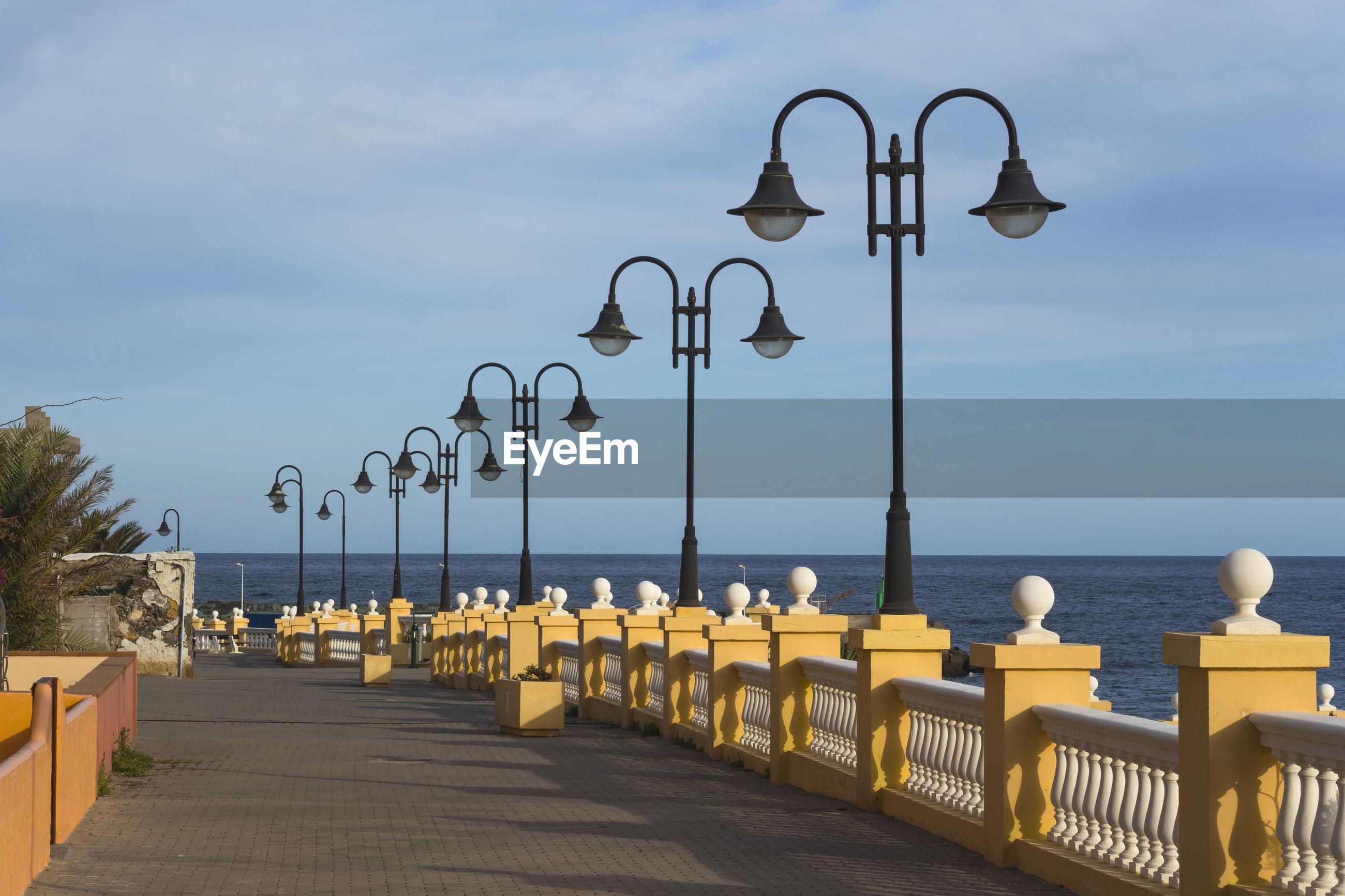STREET LIGHTS BY SEA AGAINST SKY AT BEACH