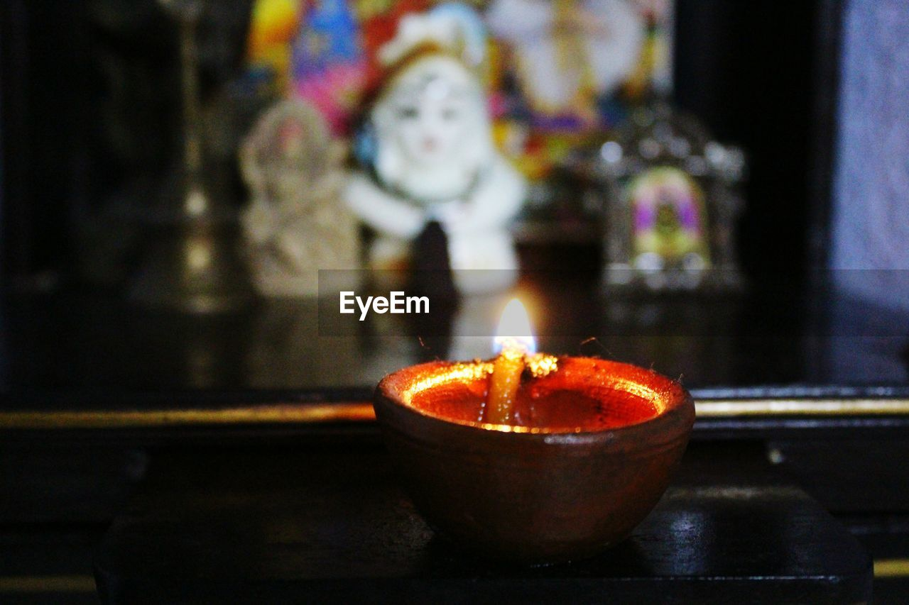 flame, burning, heat - temperature, candle, indoors, religion, spirituality, glowing, cultures, diya - oil lamp, focus on foreground, tradition, celebration, oil lamp, place of worship, no people, illuminated, close-up, diwali, night, altar