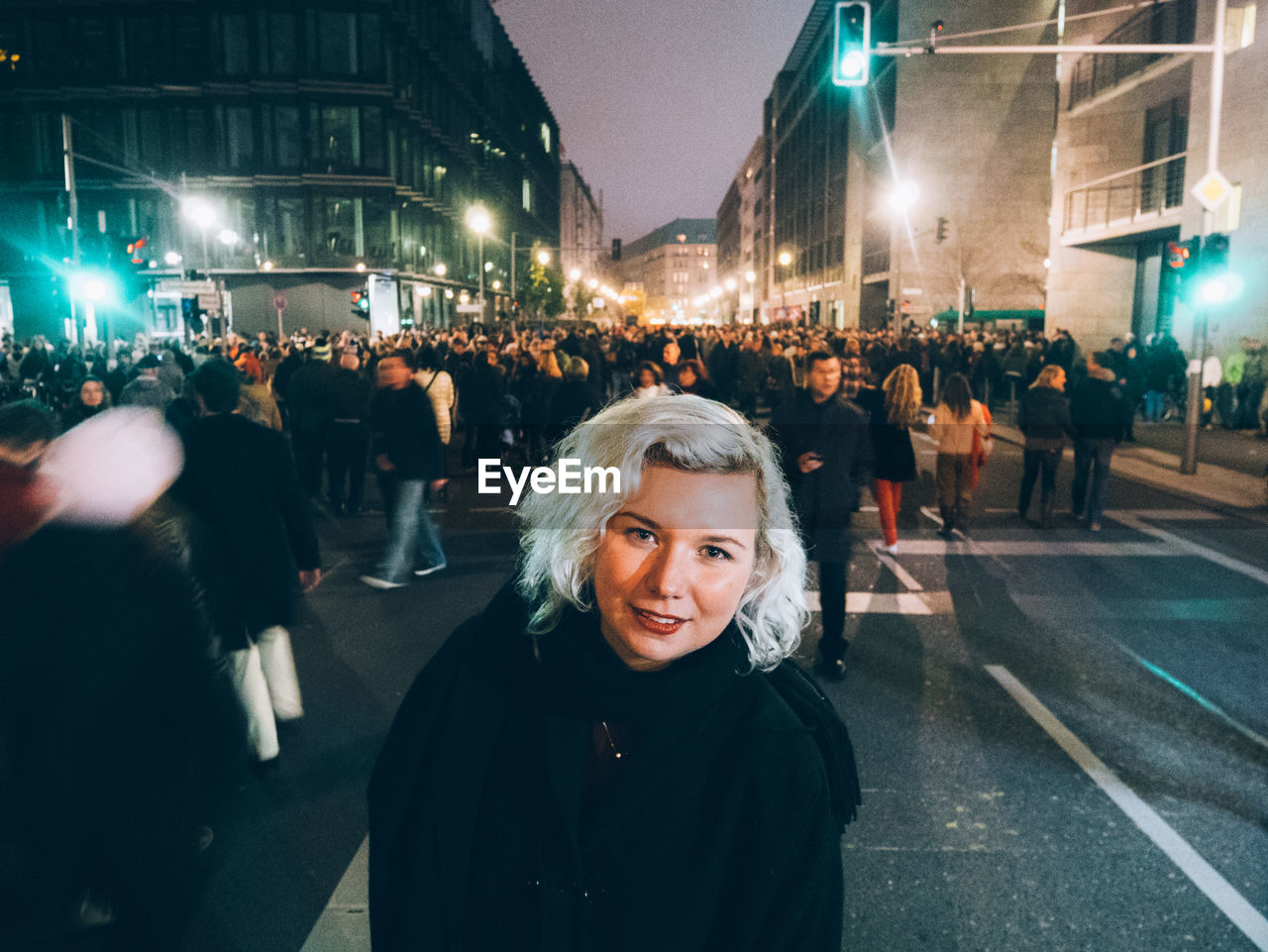 Portrait Of Smiling Young Woman Standing On Crowded Street At Night