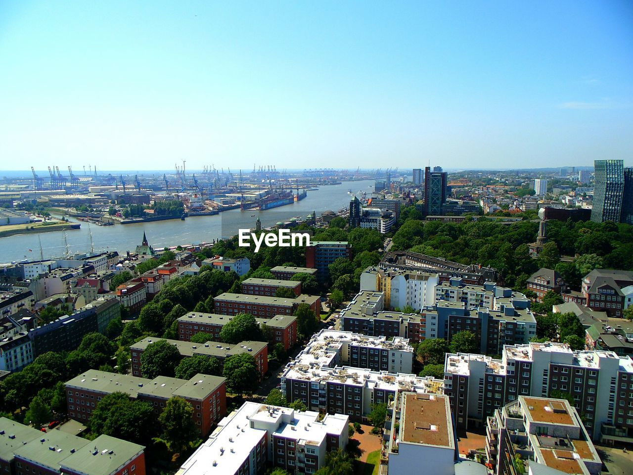 architecture, building exterior, built structure, cityscape, city, high angle view, clear sky, no people, outdoors, day, river, water, sky, residential building, skyscraper, aerial view, modern, tree, nature