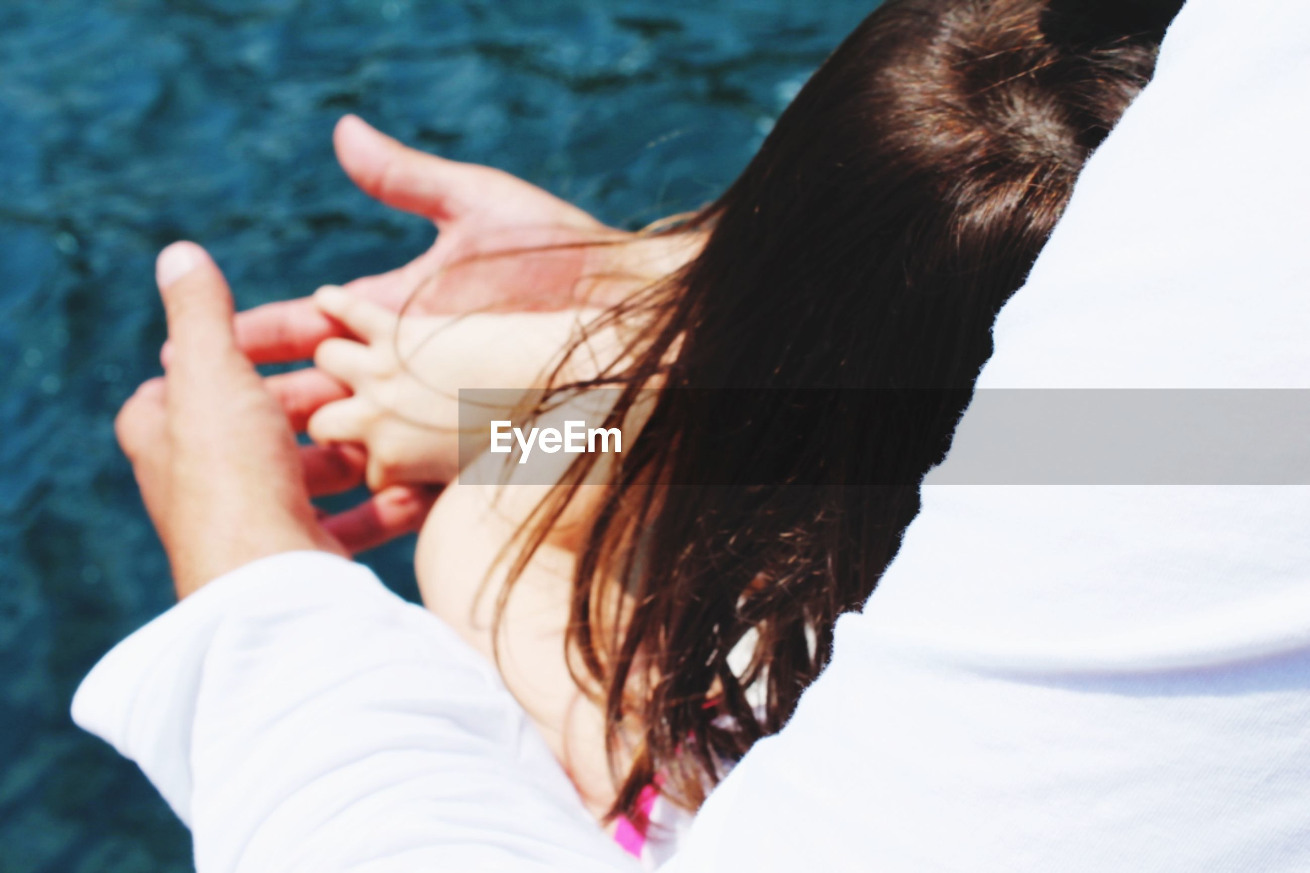 Cropped image of mother embracing daughter outdoors