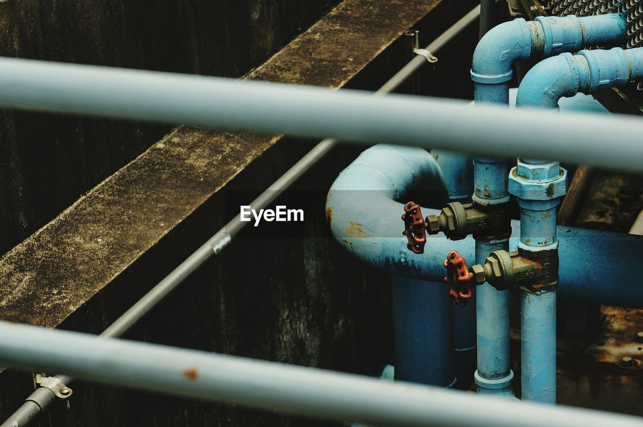 High angle view of red valves on blue metallic pipes