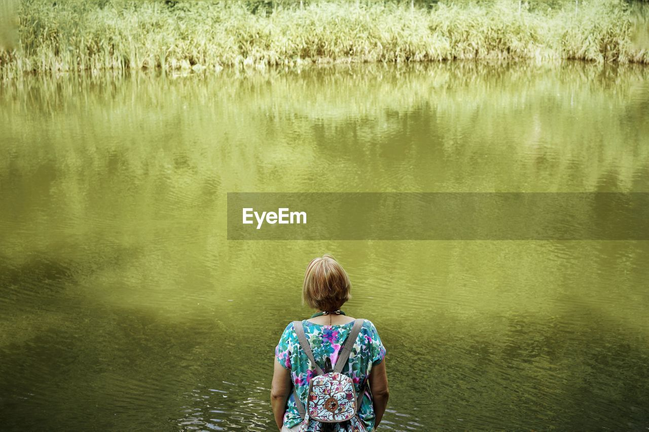 Rear View Of Senior Woman With Backpack Looking At Lake While Standing In Forest