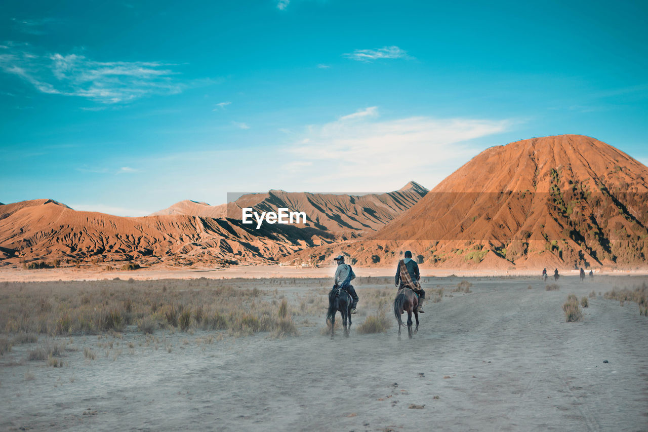 Rear View Of Men Horseback Riding At Desert Against Mountains And Sky