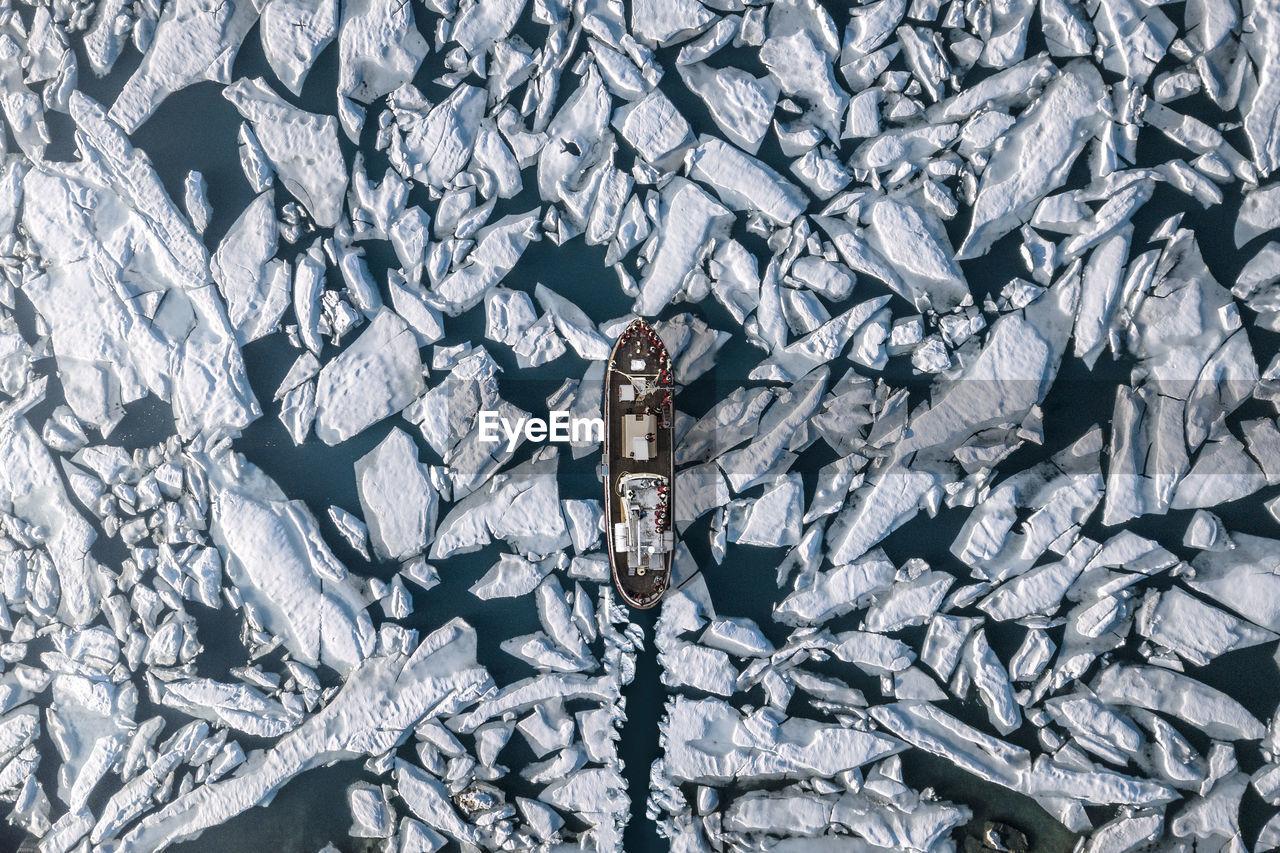 Aerial view of ship amidst glacier in sea
