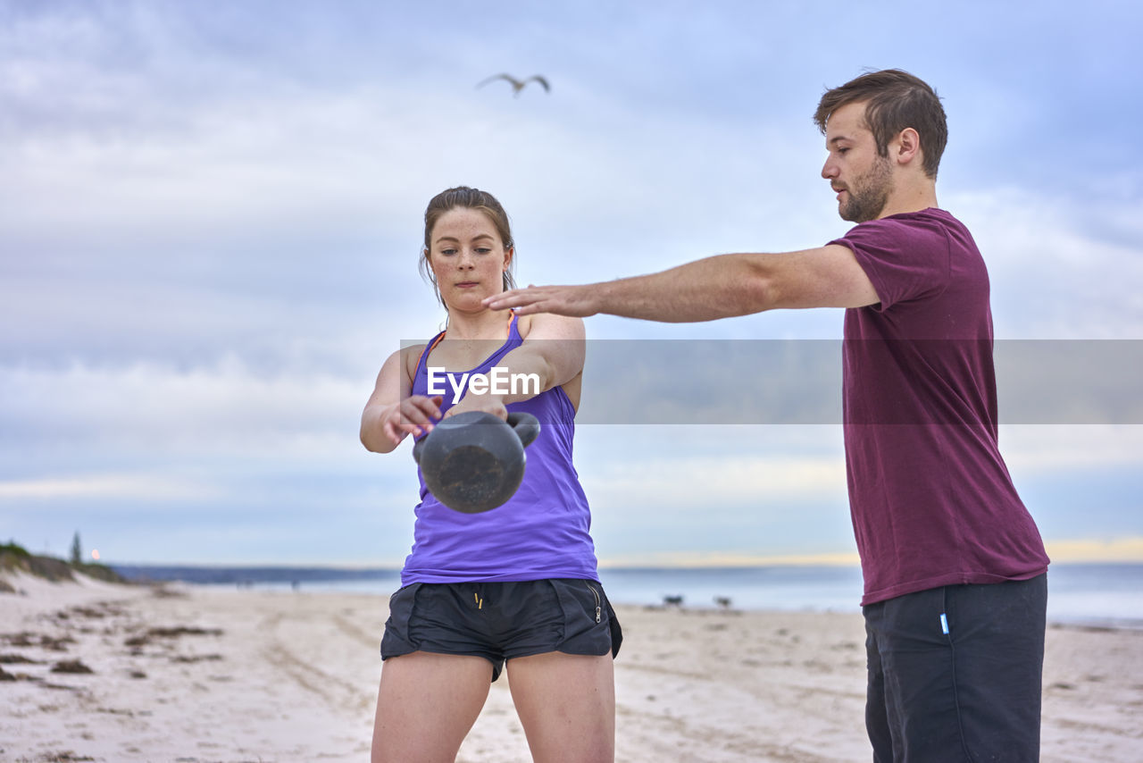 Friends Exercising At Beach Against Sky