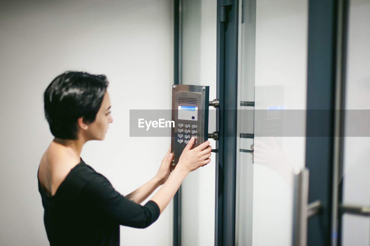 Woman Pressing Button On Door At Home