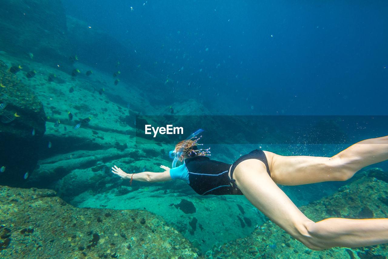 Woman snorkeling over coral reef undersea