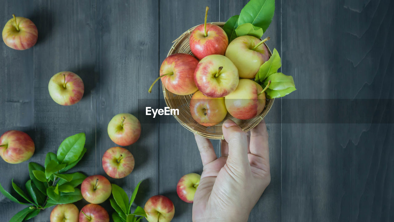 food and drink, freshness, healthy eating, food, wellbeing, fruit, one person, holding, human body part, human hand, hand, apple - fruit, real people, directly above, unrecognizable person, body part, table, day, large group of objects, finger, human limb