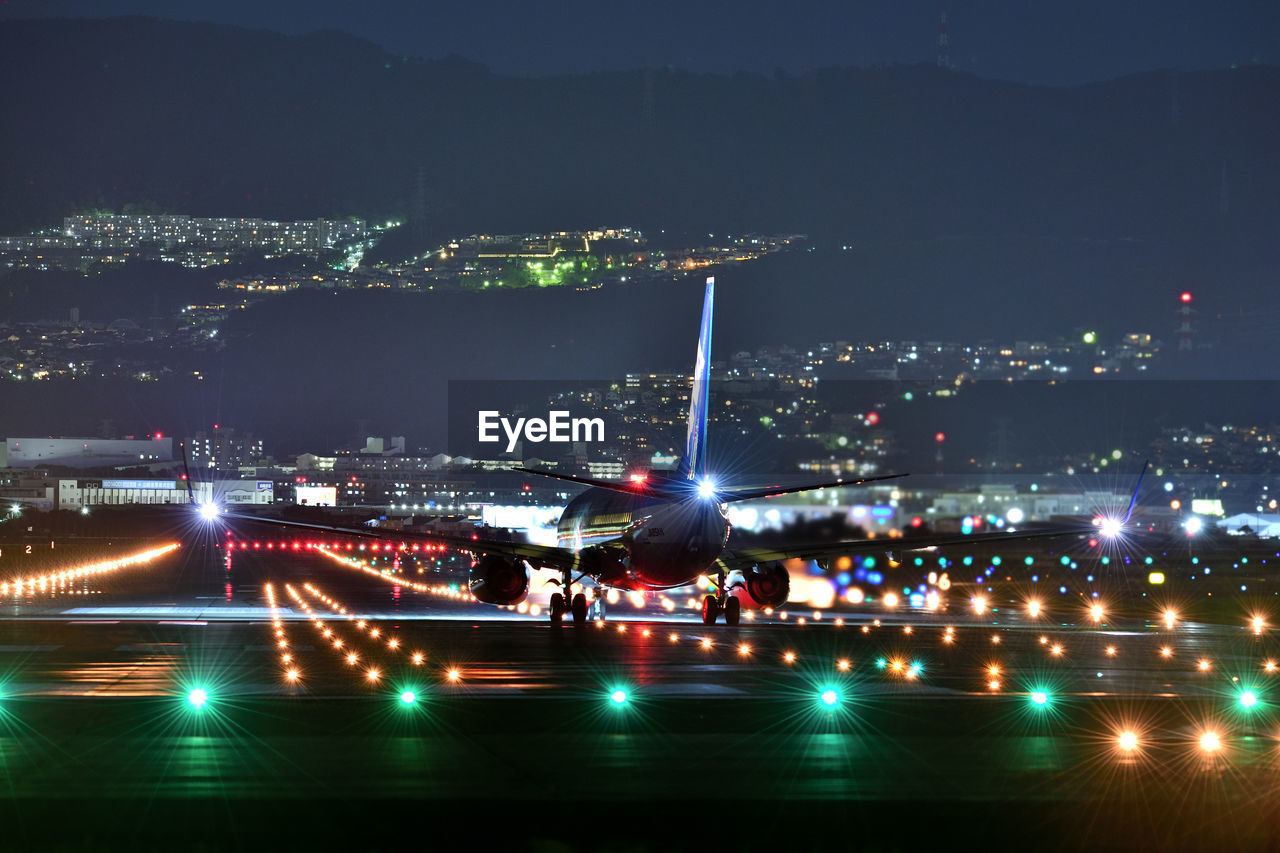 illuminated, night, architecture, city, motion, built structure, building exterior, transportation, cityscape, crowd, arts culture and entertainment, mode of transportation, city life, sky, travel, blurred motion, outdoors, airport runway, nature, airplane, light