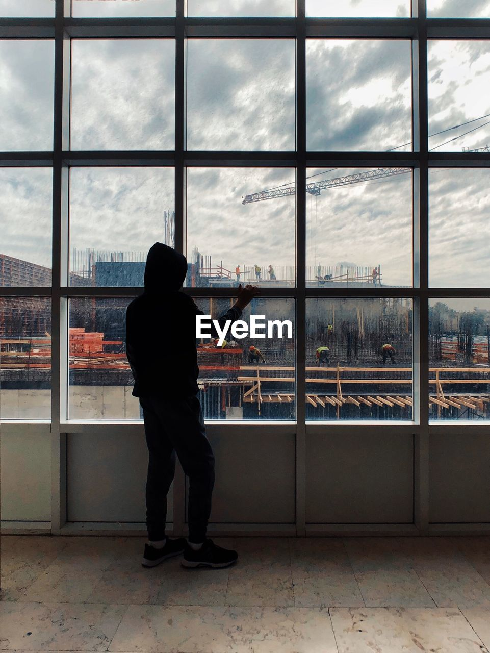 Rear View Of Man Looking At Construction Site Through Window