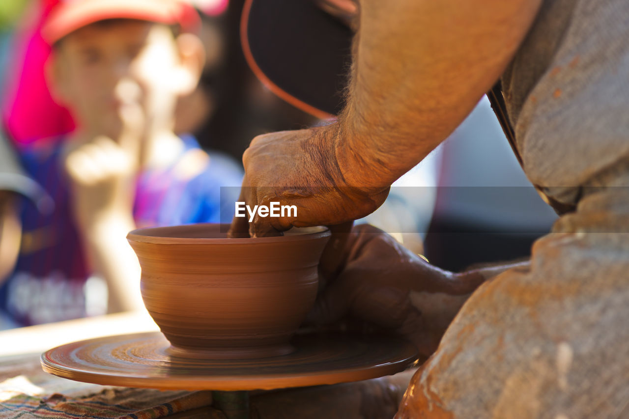 Midsection Of Potter Making Bowl In Market