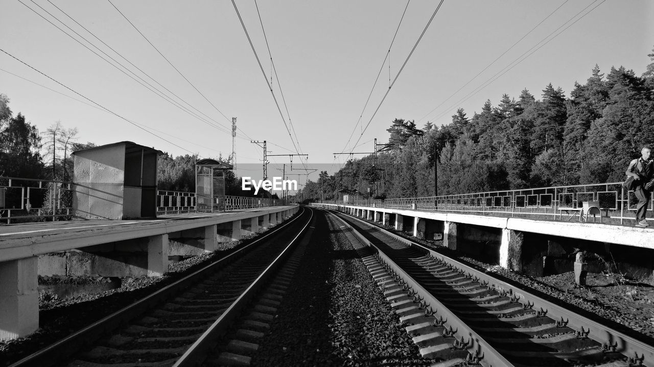 track, railroad track, rail transportation, transportation, electricity, cable, sky, diminishing perspective, tree, plant, the way forward, connection, nature, power line, day, direction, no people, technology, mode of transportation, public transportation, outdoors, power supply, straight, long