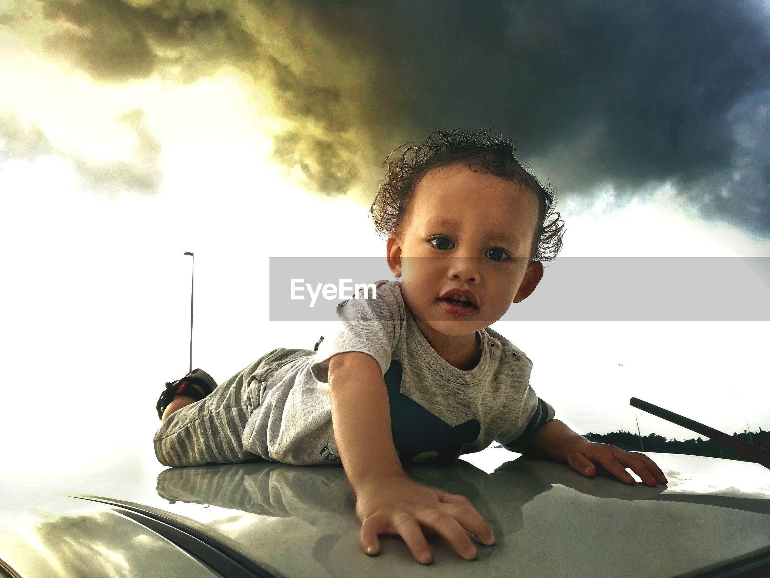 Portrait of cute boy on car roof against cloudy sky