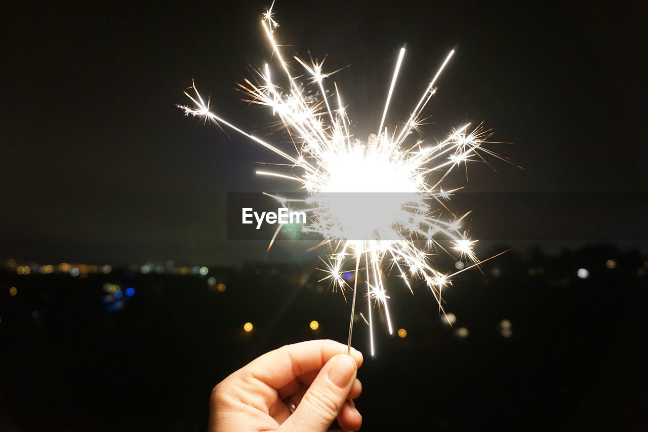 human hand, celebration, night, holding, firework - man made object, illuminated, exploding, sparkler, firework display, focus on foreground, real people, human body part, long exposure, outdoors, burning, close-up, sky, one person, firework, people