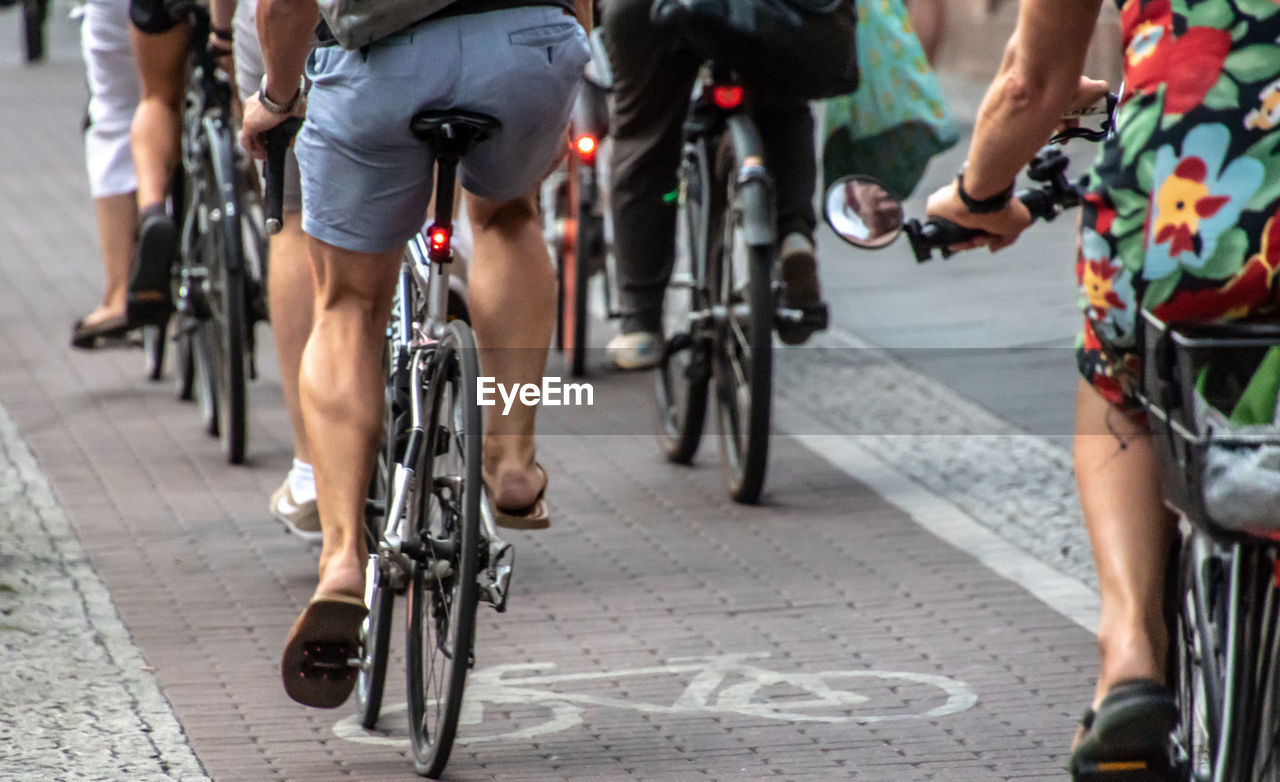 Low Section Of People Riding Bicycles On Road
