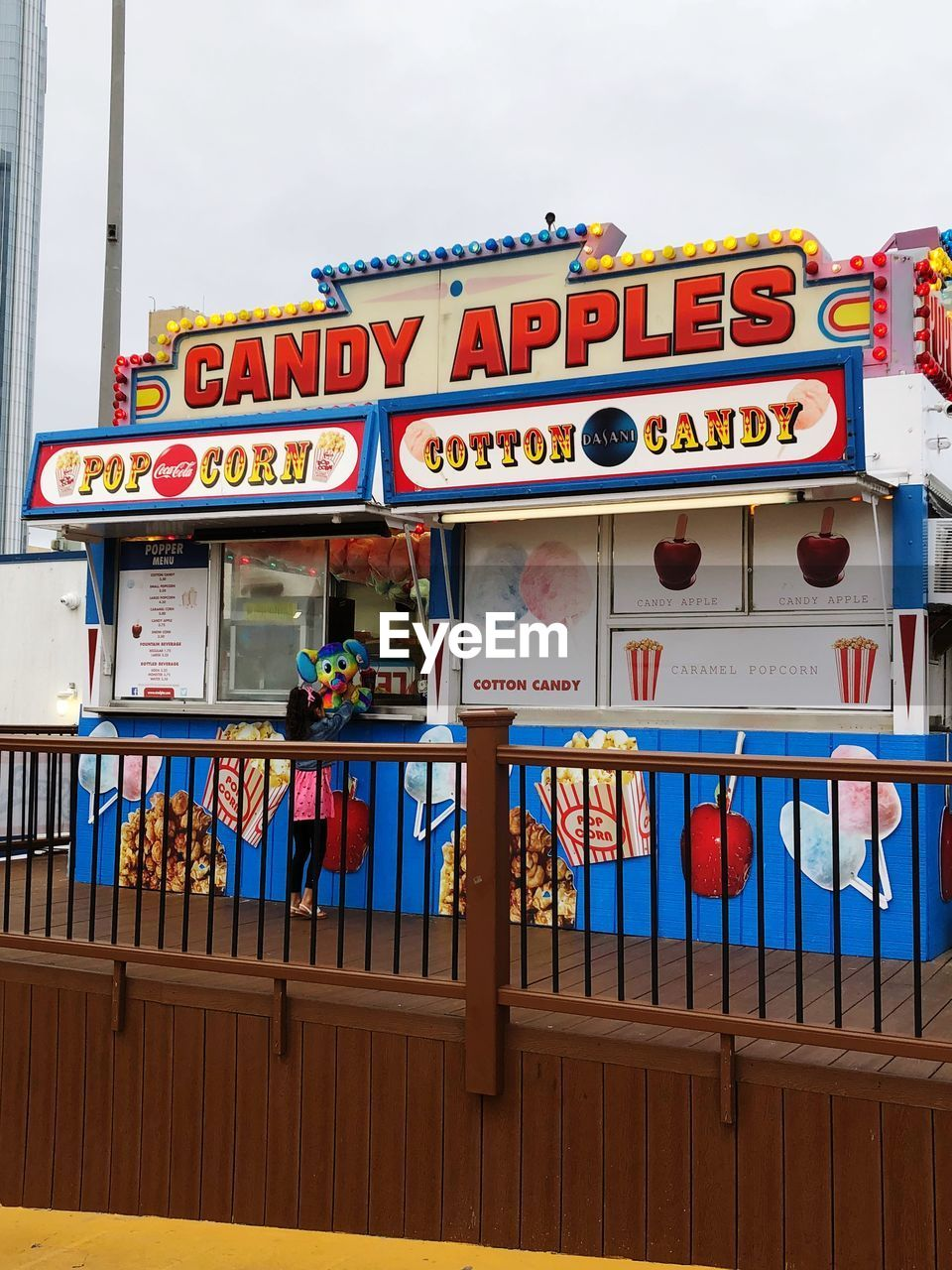 text, western script, architecture, communication, built structure, no people, railing, day, building exterior, multi colored, sign, outdoors, sky, food and drink, capital letter, arts culture and entertainment, wood - material, low angle view, table