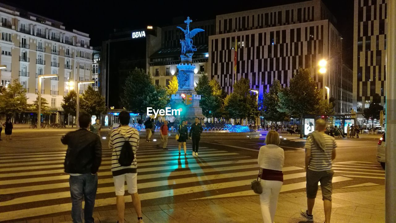 architecture, night, illuminated, built structure, city, building exterior, city life, real people, outdoors, large group of people, tree, people