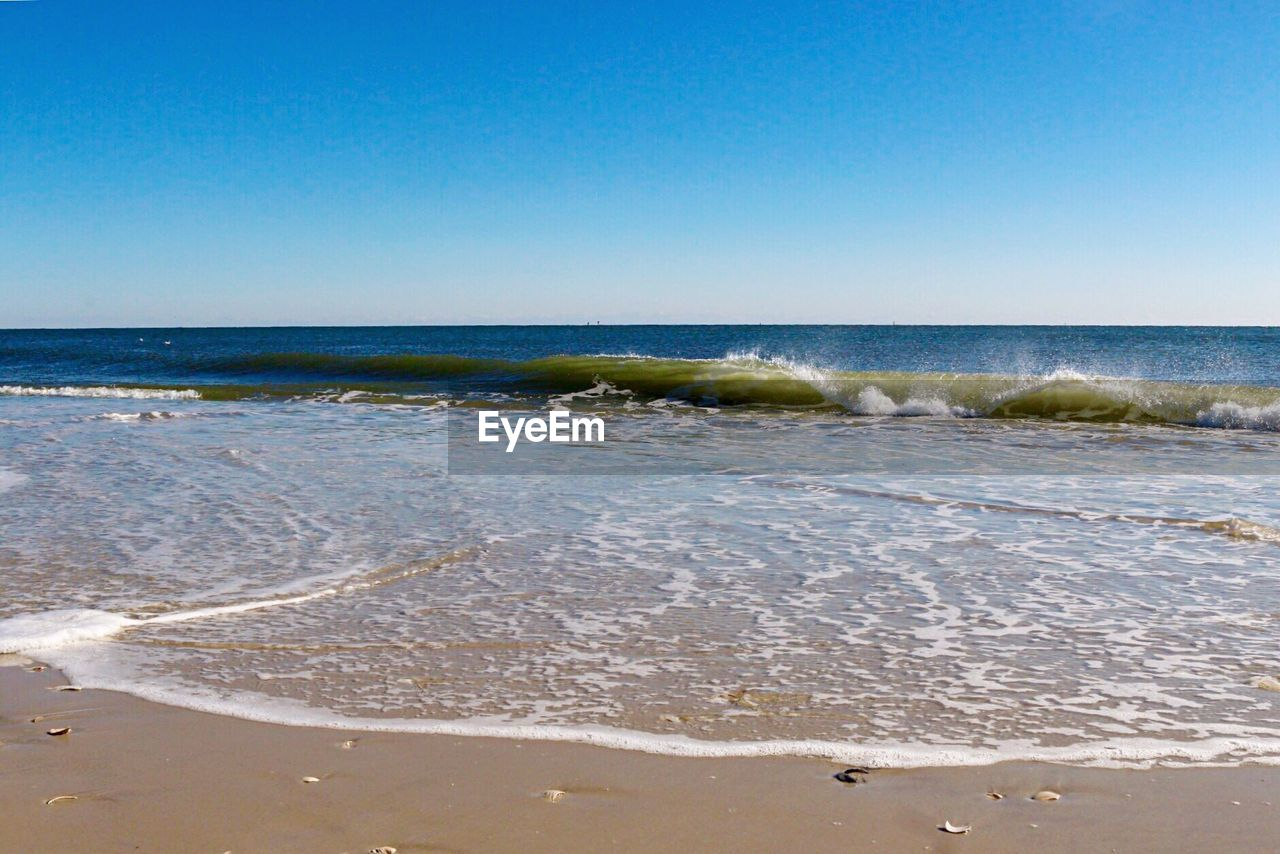 sea, wave, beach, clear sky, horizon over water, beauty in nature, nature, scenics, water, shore, sand, no people, blue, tranquility, day, tranquil scene, outdoors, sky