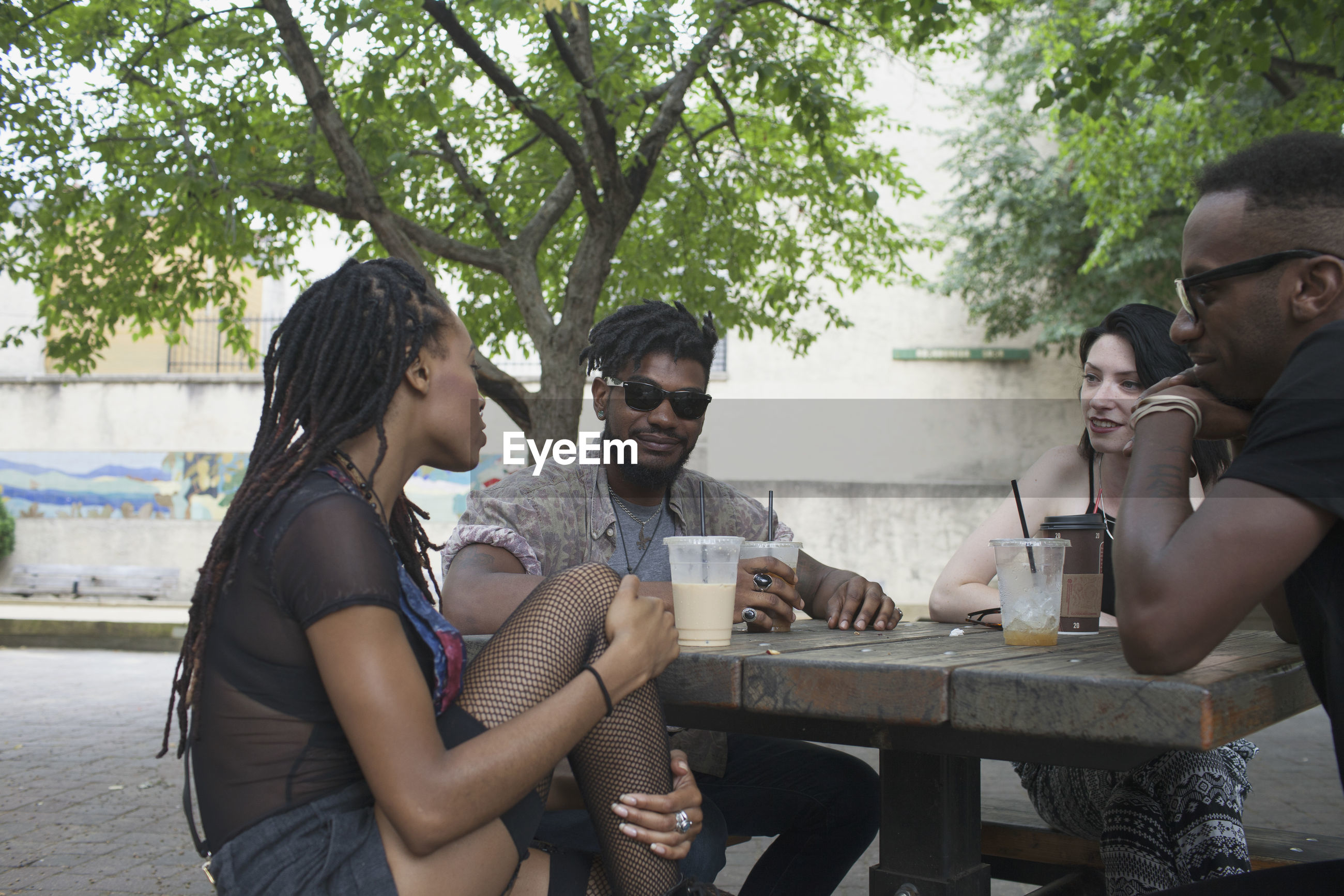 YOUNG COUPLE SITTING ON TABLE AT PARK