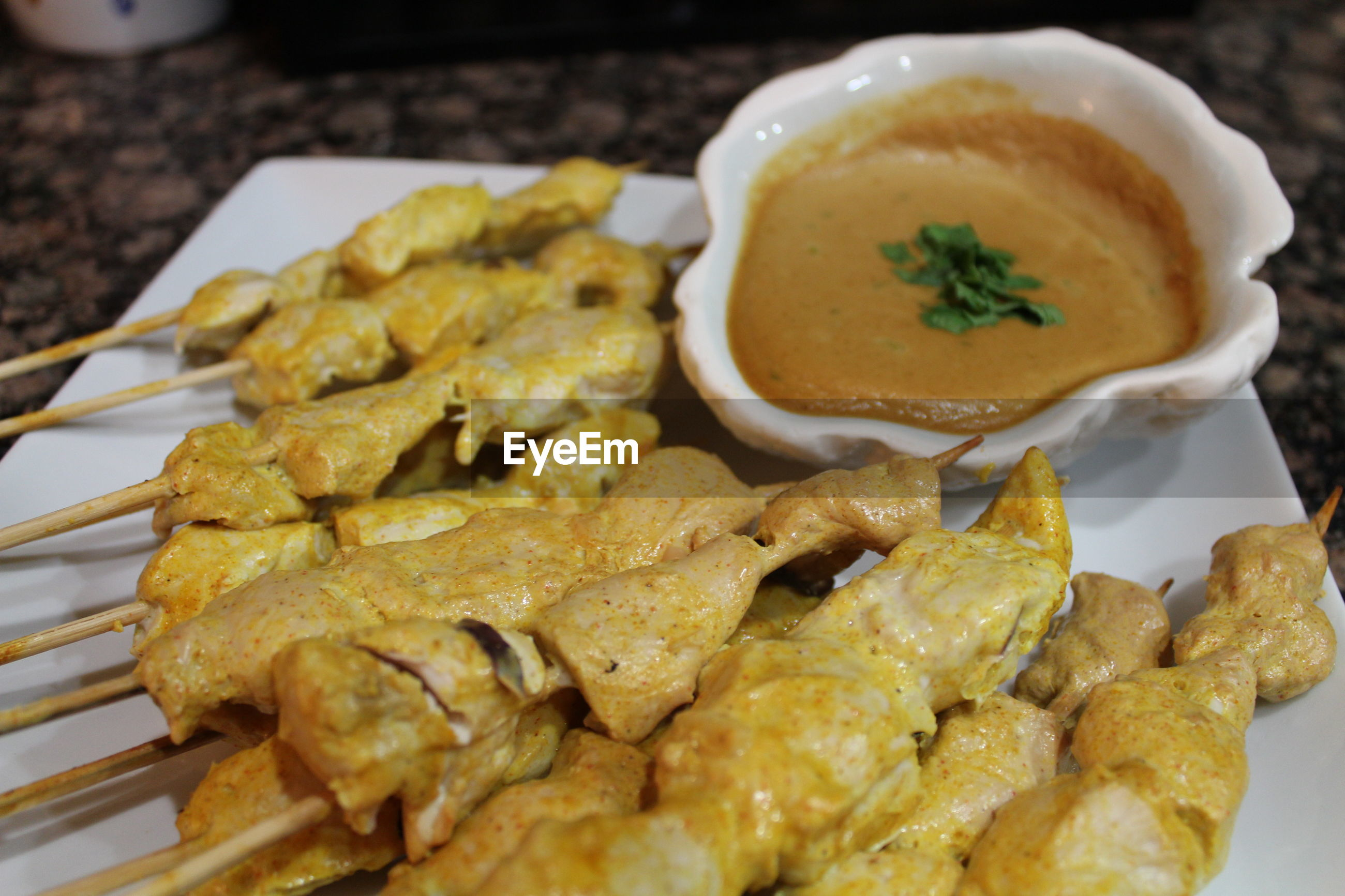 High angle view of chicken skewers served with peanut sauce in plate