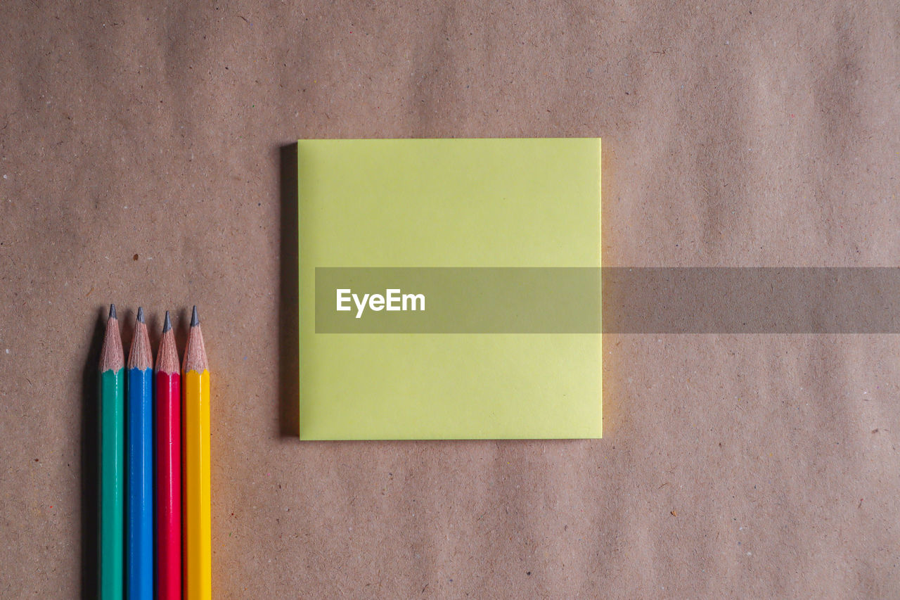 multi colored, pencil, note, writing instrument, paper, no people, indoors, close-up, adhesive note, copy space, art and craft, blank, still life, yellow, colored pencil, variation, choice, craft, art and craft equipment, office supply, note pad