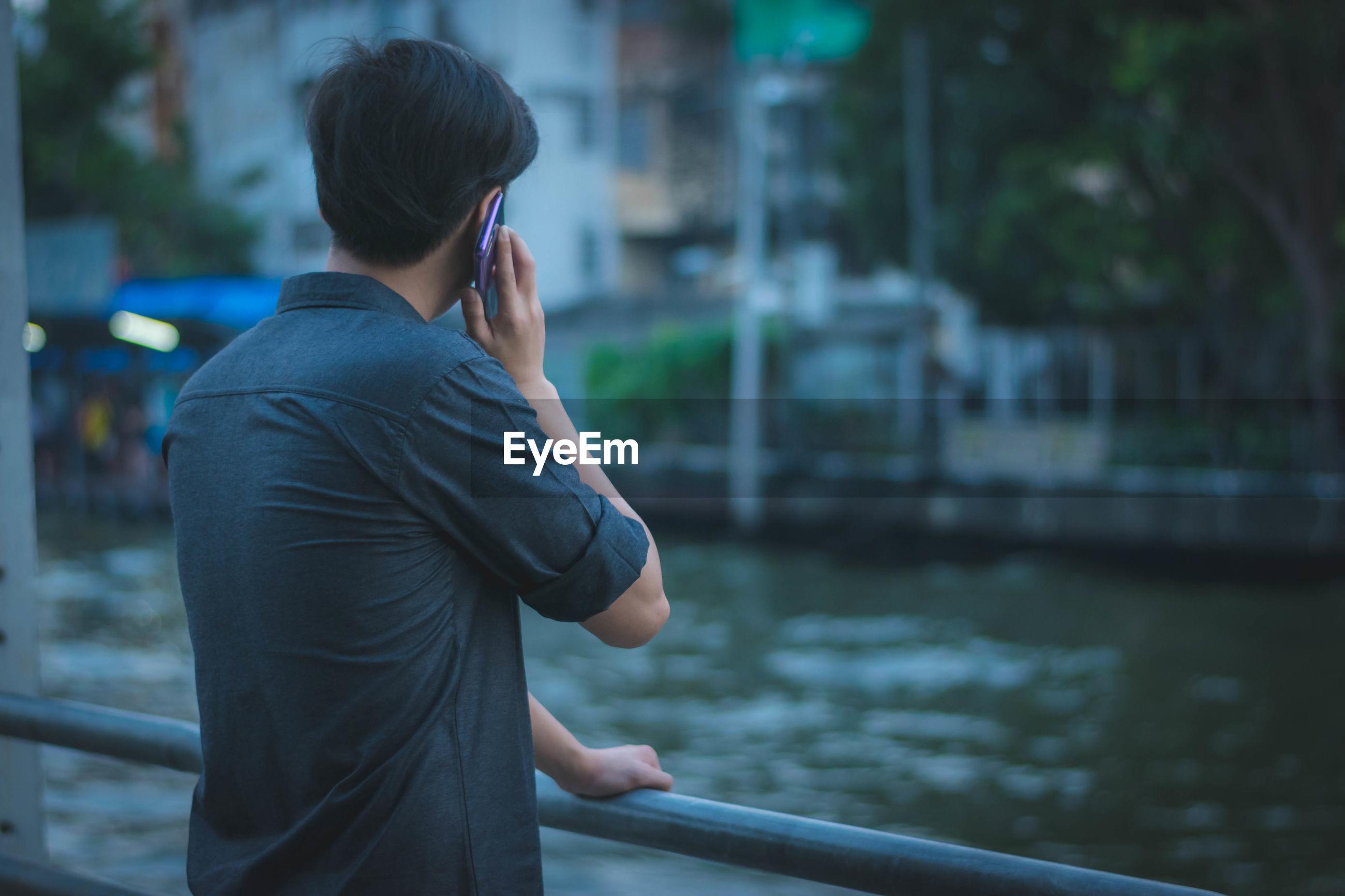 Man talking on mobile phone against pond