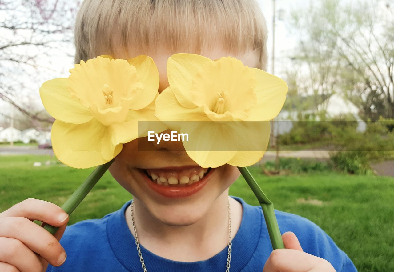 Close-up of smiling boy covering eyes with yellow orchids at park