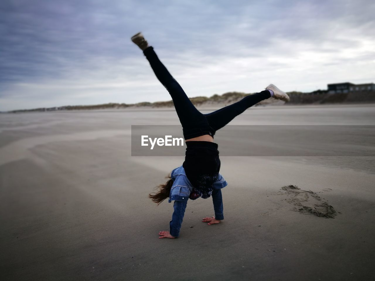 Full Length Of Girl Practicing Handstand At Beach Against Sky