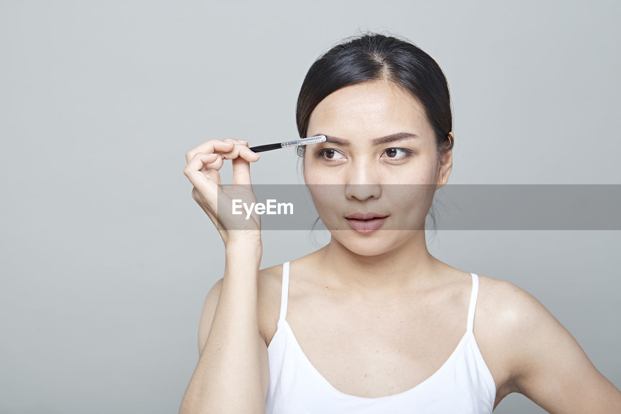 Close-Up Of Woman Brushing Eyebrow Against Gray Background