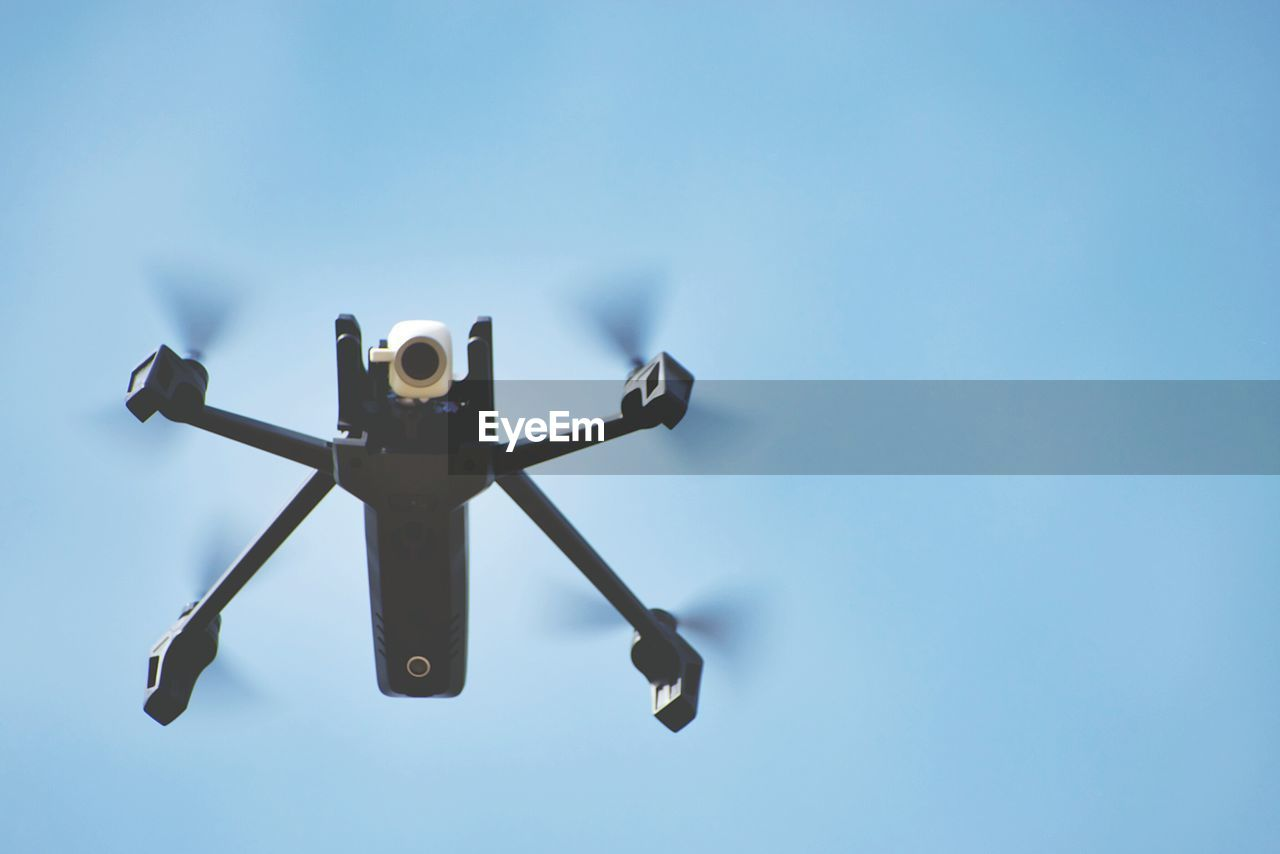 Low angle view of flying drone against sky