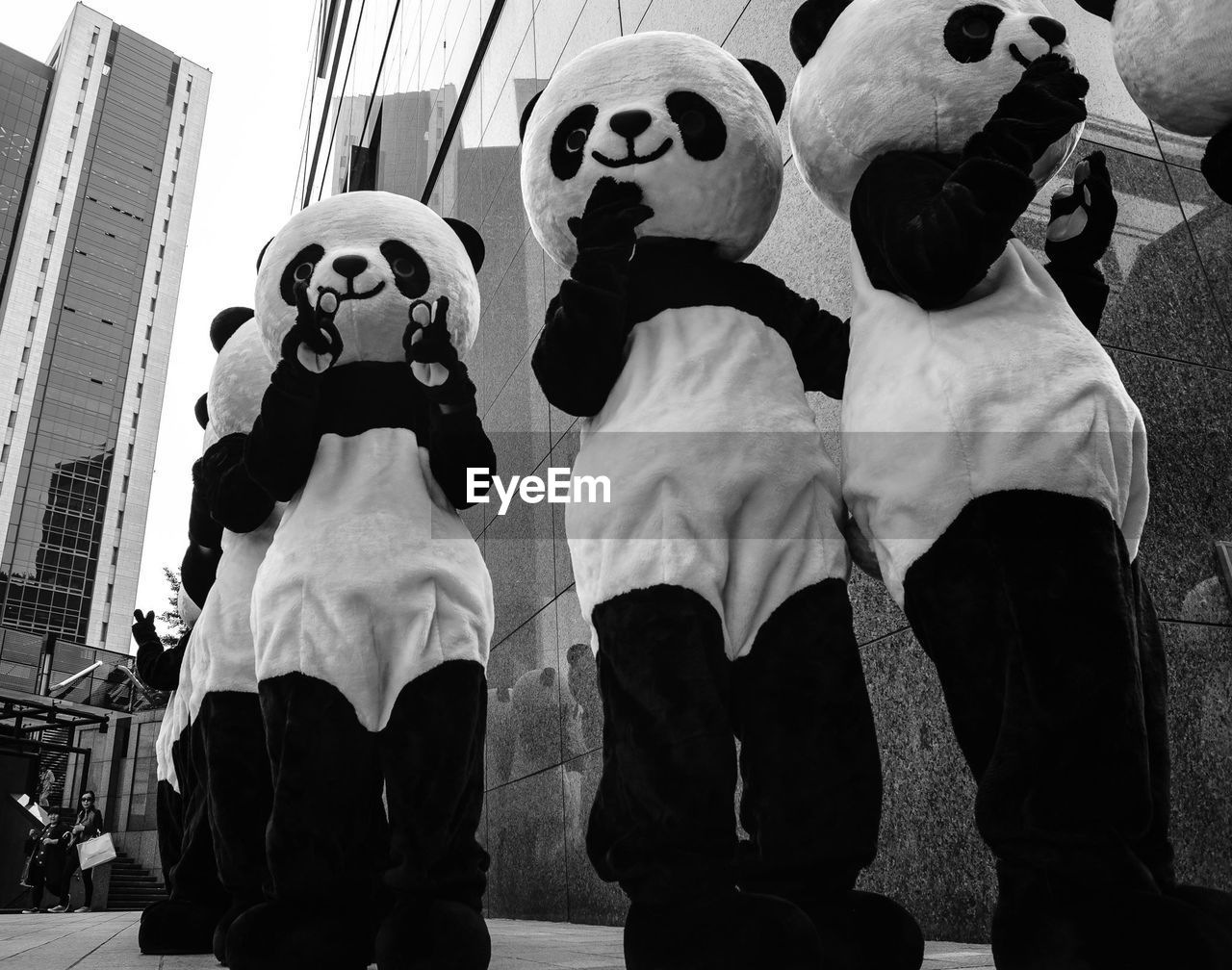 Low Angle View Of People Wearing Panda Costume Standing On Street