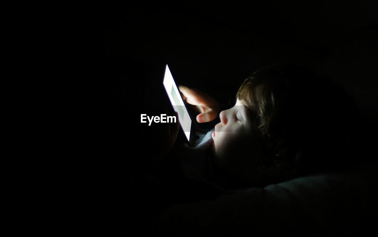 Close-Up Of Boy Using Mobile Phone In Darkroom