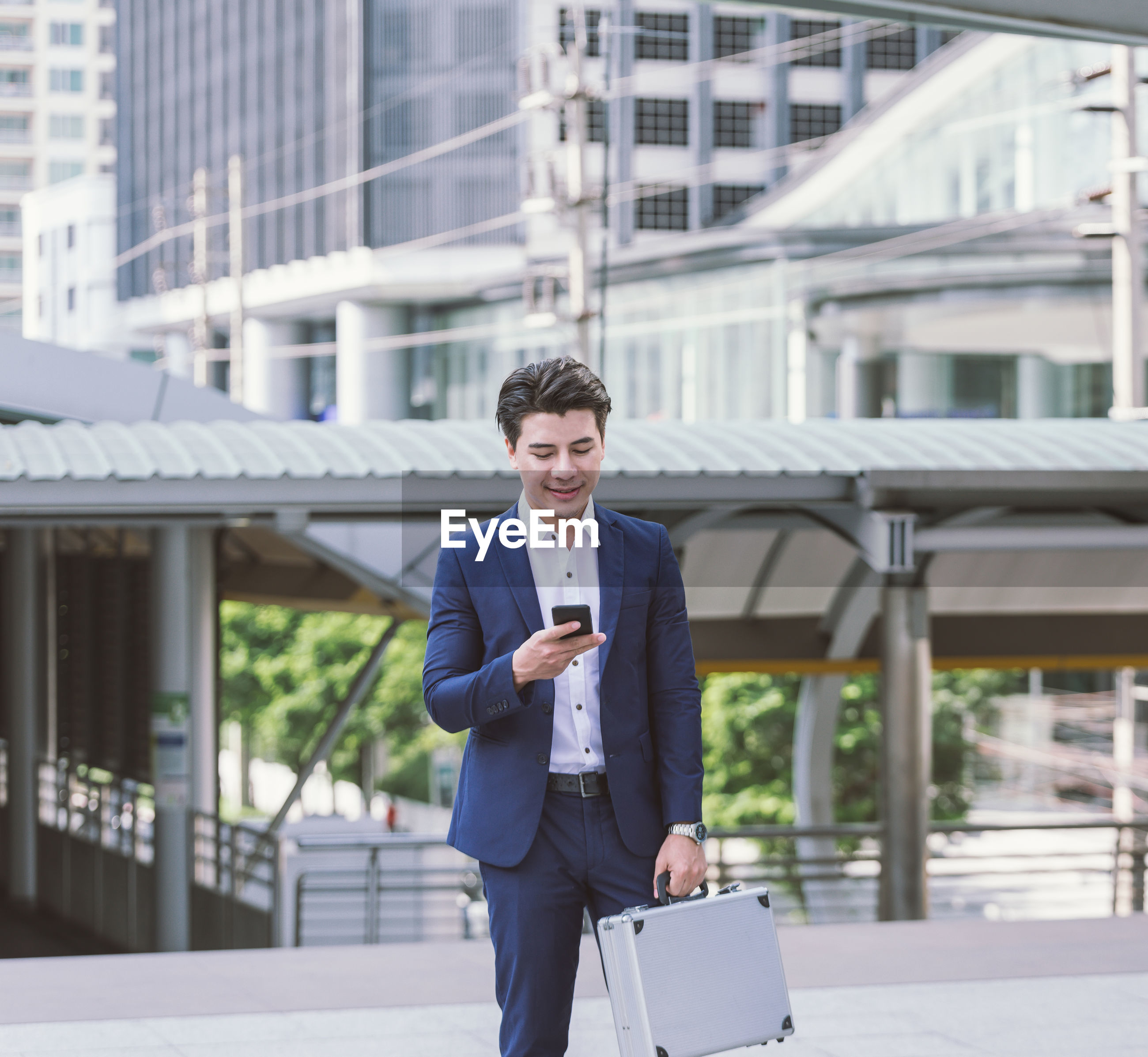 Happy young businessman using phone while standing in city against building
