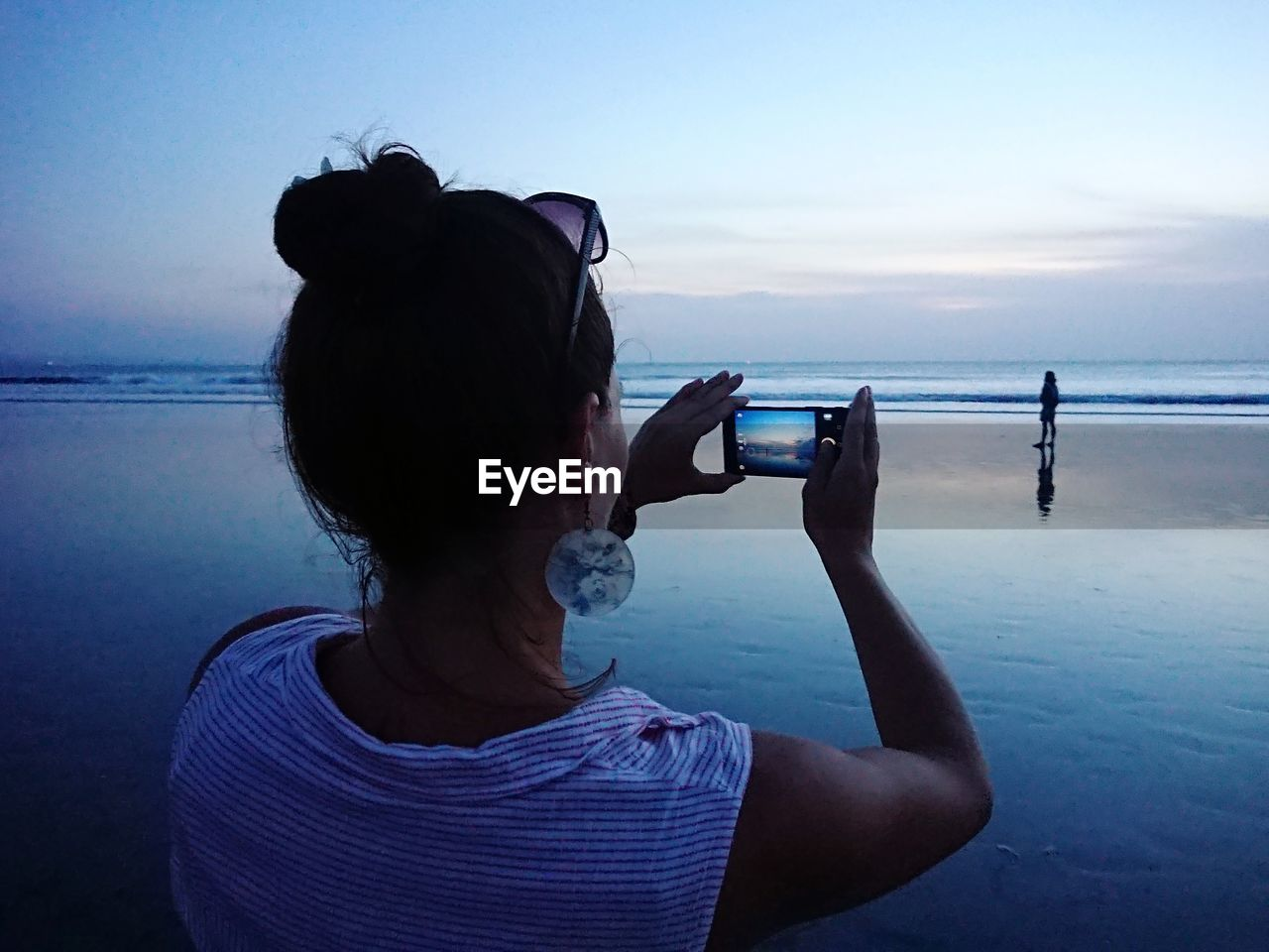 REAR VIEW OF WOMAN PHOTOGRAPHING SEA THROUGH CAMERA