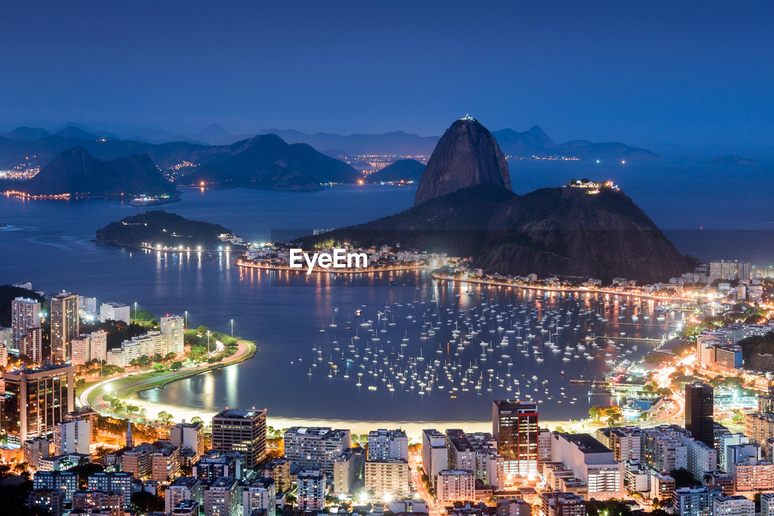 Illuminated cityscape and sugarloaf mountain by guanabara bay