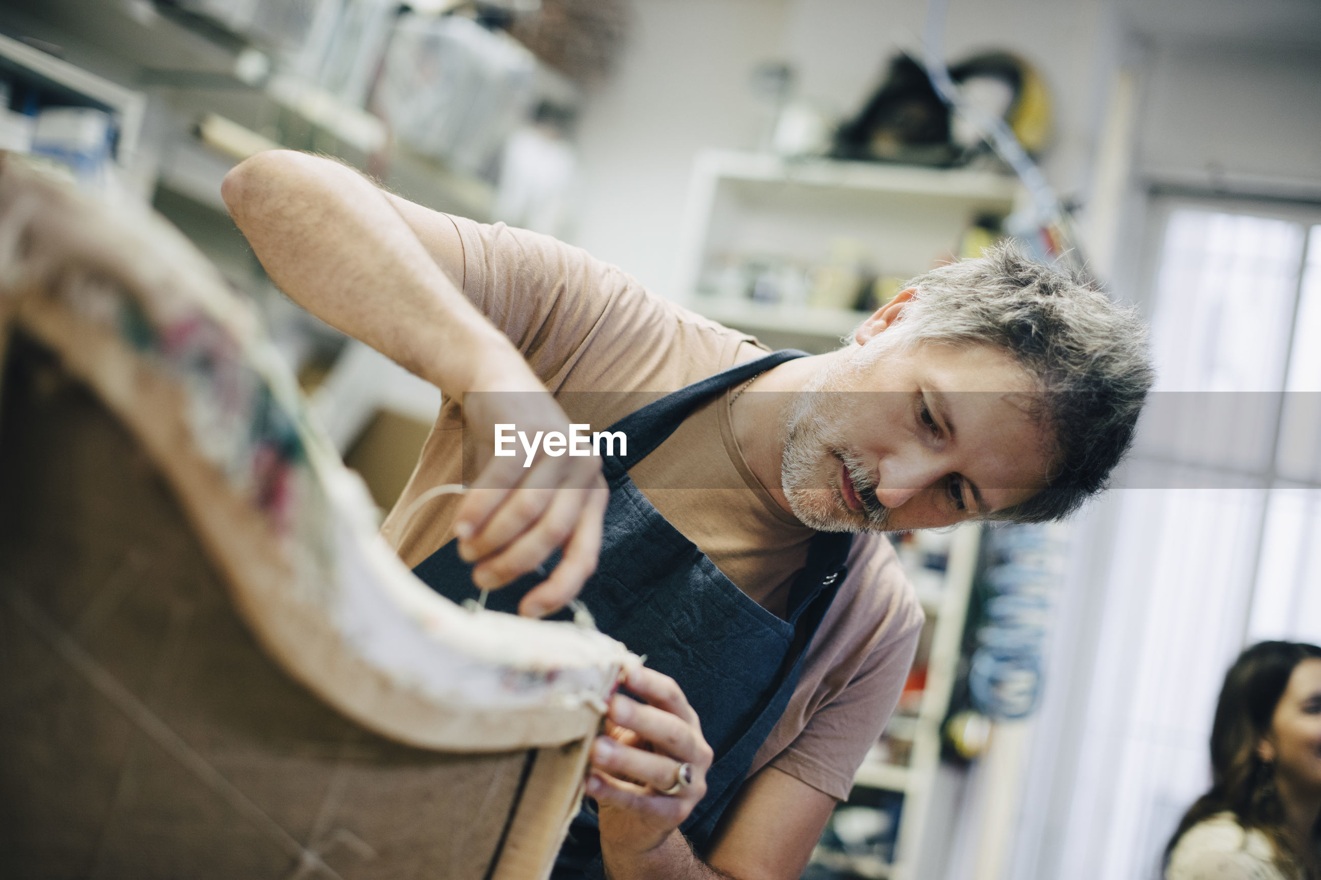 Mature craftsperson stitching furniture in workshop