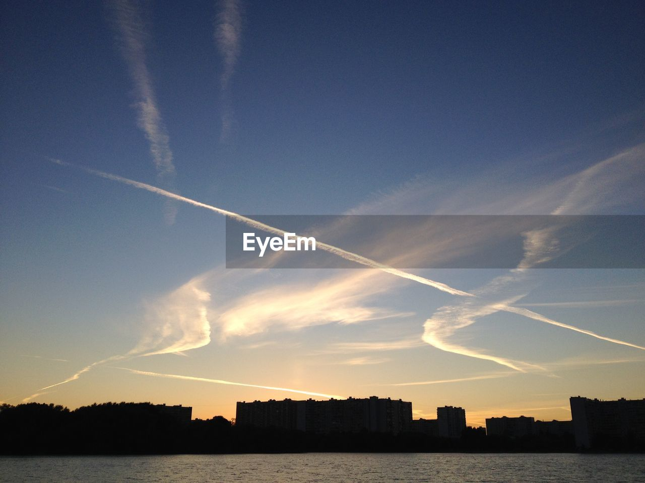 vapor trail, contrail, sky, no people, nature, sunset, built structure, scenics, water, outdoors, architecture, beauty in nature, building exterior, day