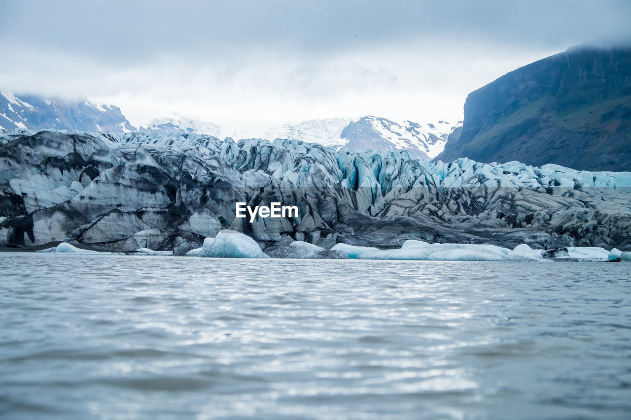 Scenic view of glaciers and mountains against cloudy sky