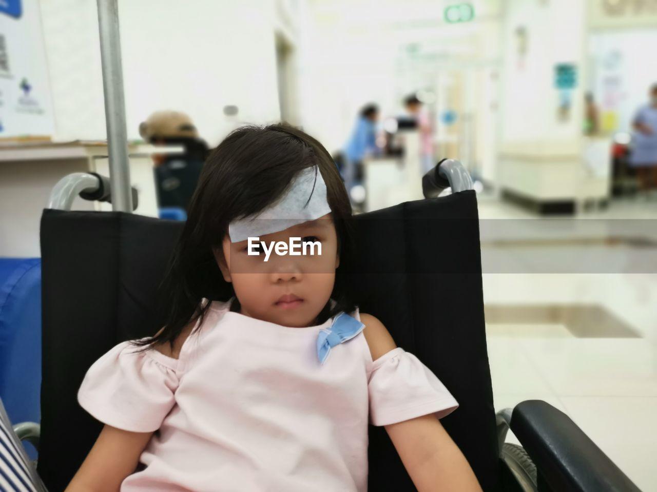 Girl sitting on wheelchair in hospital