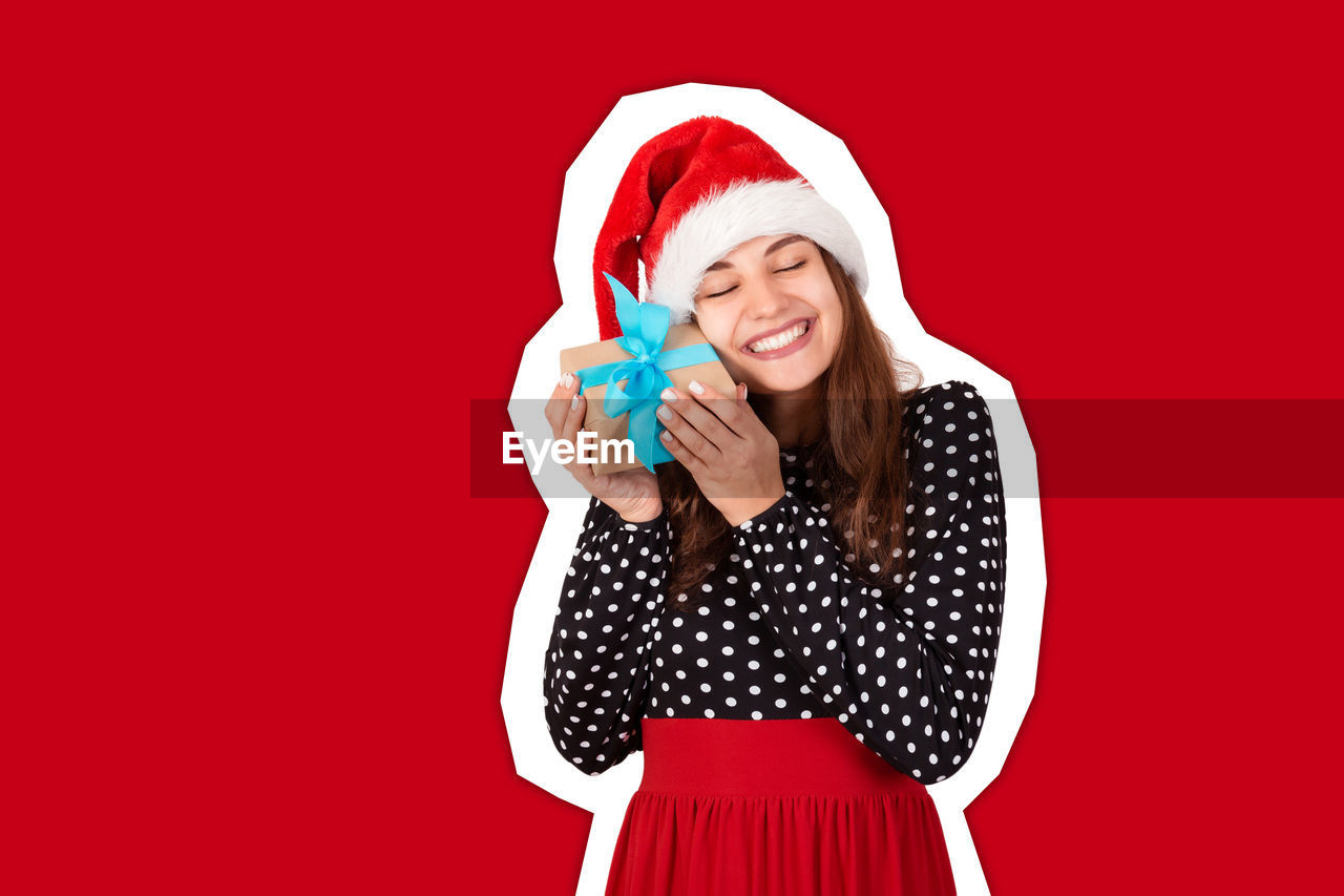 Digital composite image of smiling woman holding gift while standing against red background