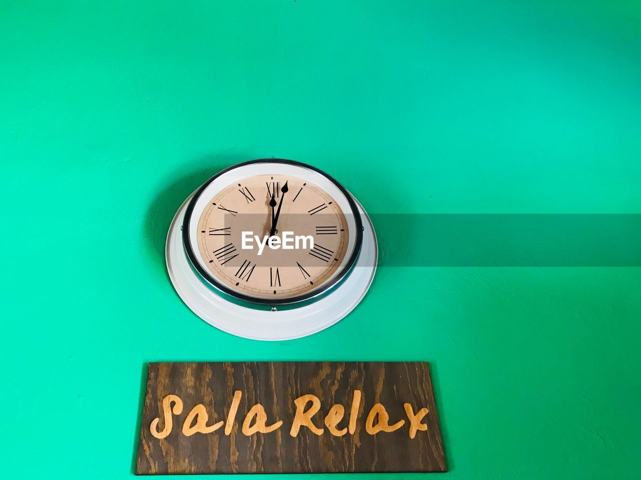 Close-up of wall clock and text on blue background