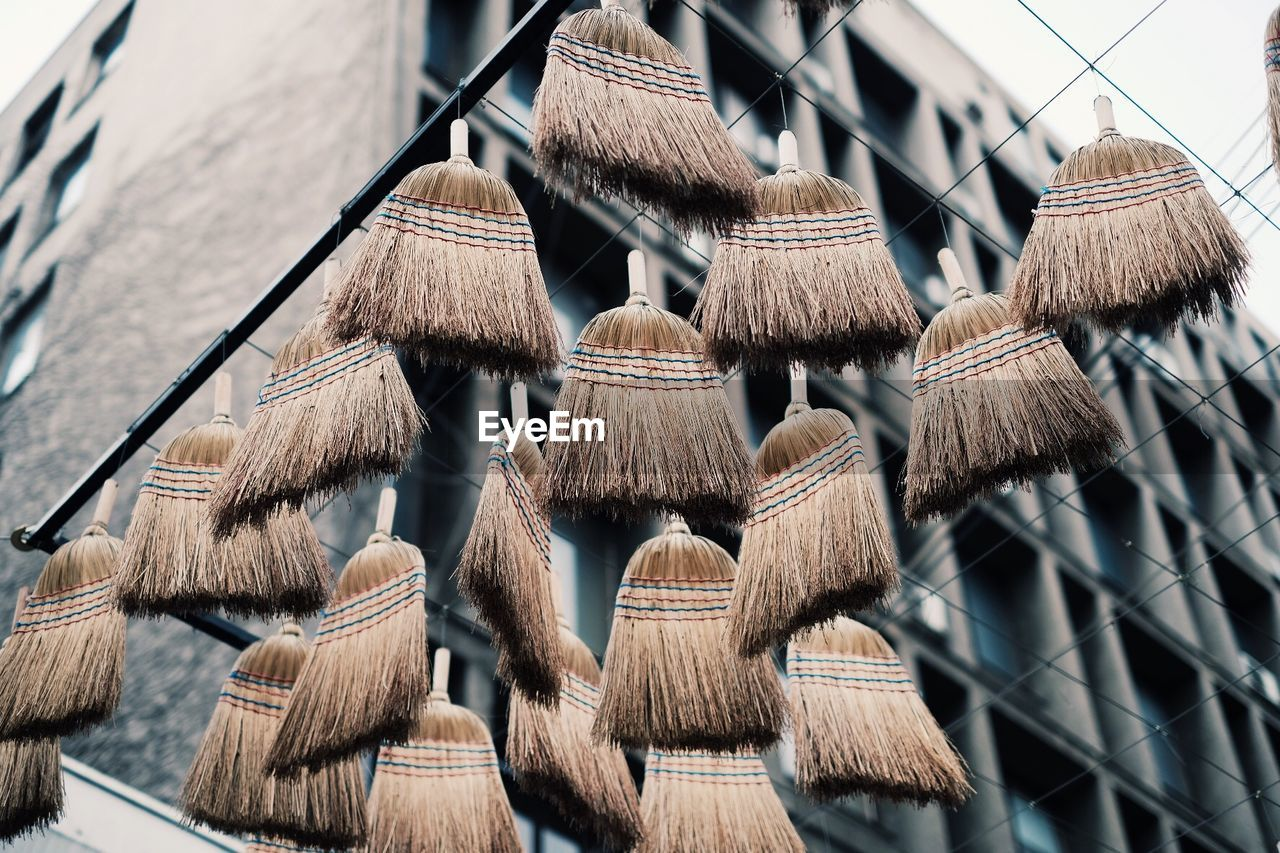 Low Angle View Of Brooms Hanging Against Building