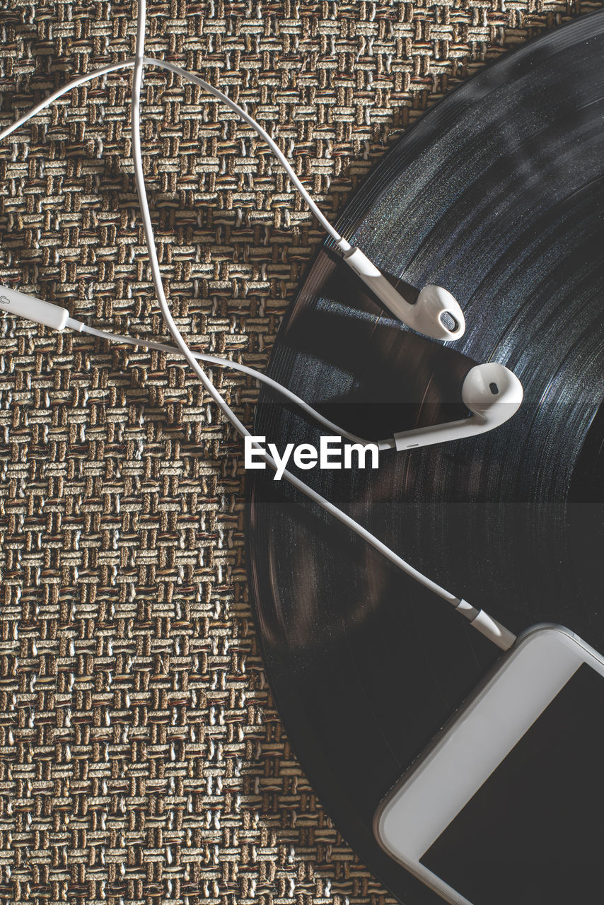indoors, high angle view, still life, close-up, no people, cable, technology, music, directly above, table, headphones, in-ear headphones, black color, arts culture and entertainment, equipment, needle, connection, pattern, listening, art and craft