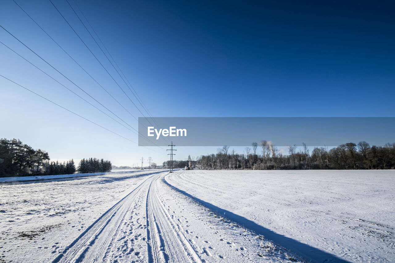 snow, cold temperature, winter, sky, cable, covering, scenics - nature, rail transportation, track, no people, nature, tree, transportation, environment, beauty in nature, electricity, railroad track, landscape, technology, outdoors, power supply, snowcapped mountain