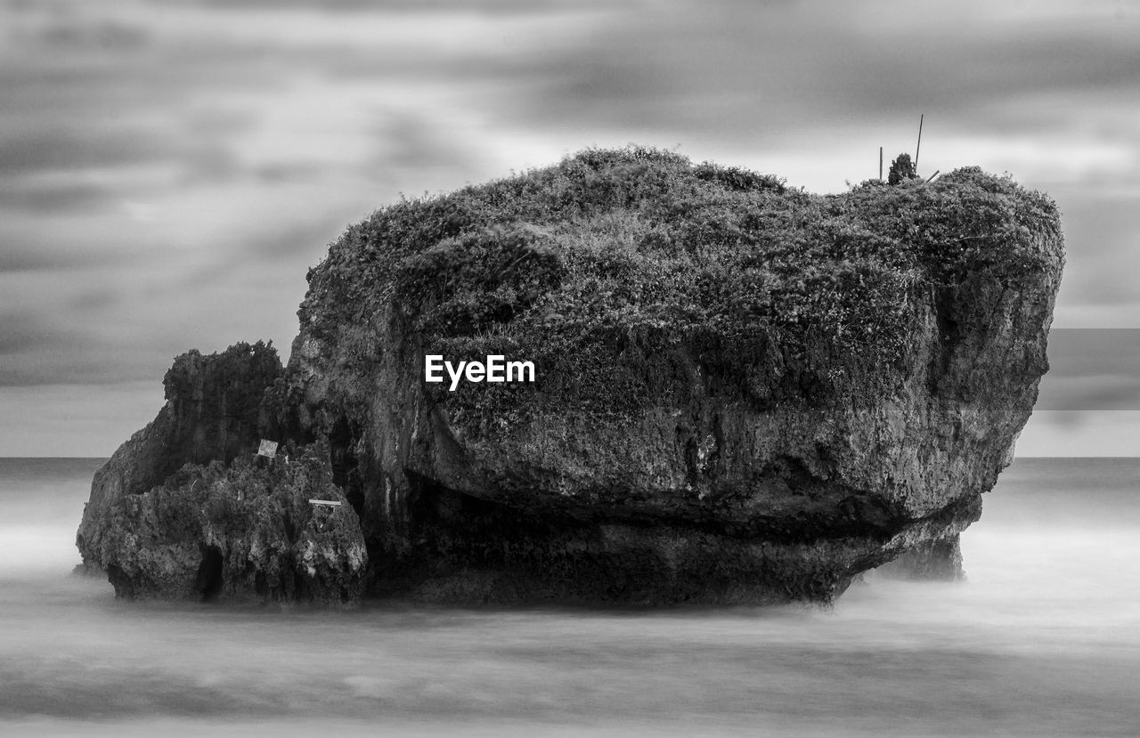 Stack rock in sea against cloudy sky