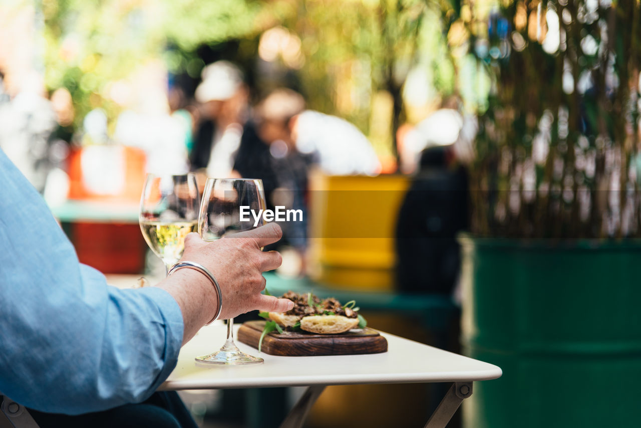 Woman enjoying meal with white wine in a trendy shopping area sitting on a terrace.