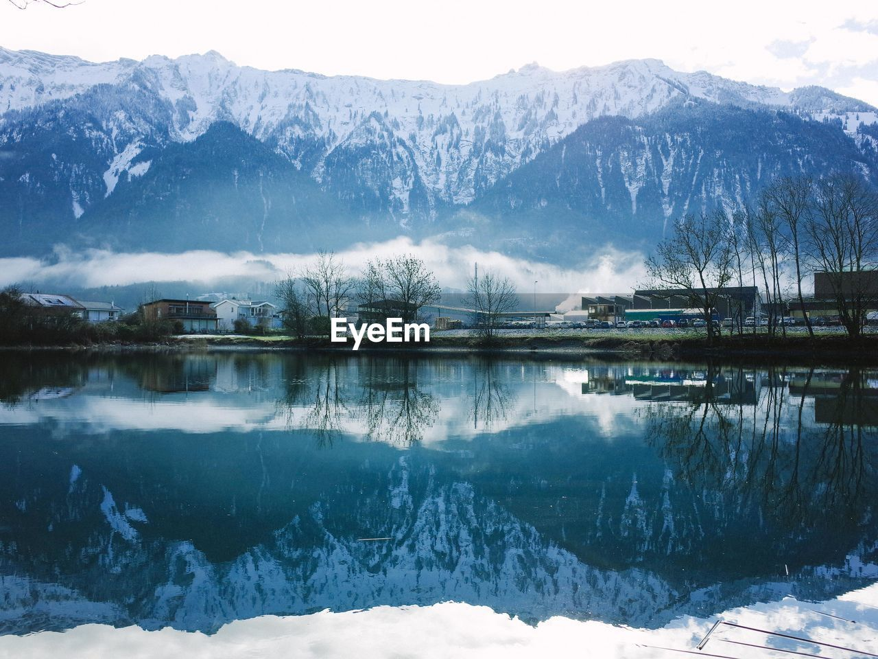 Reflection Of Snow Covered Mountains On Calm Lake