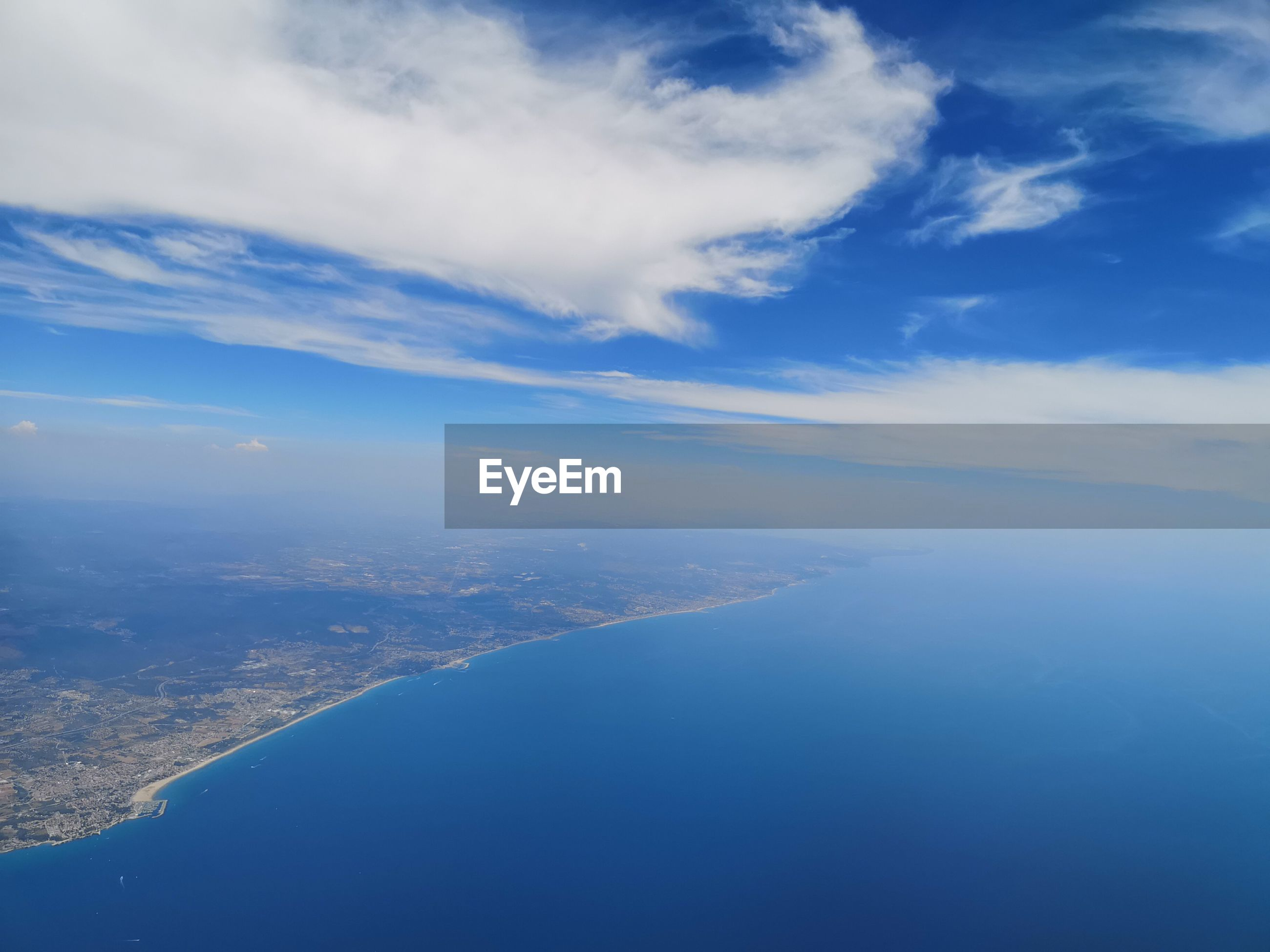 Aerial view of sea and land against sky